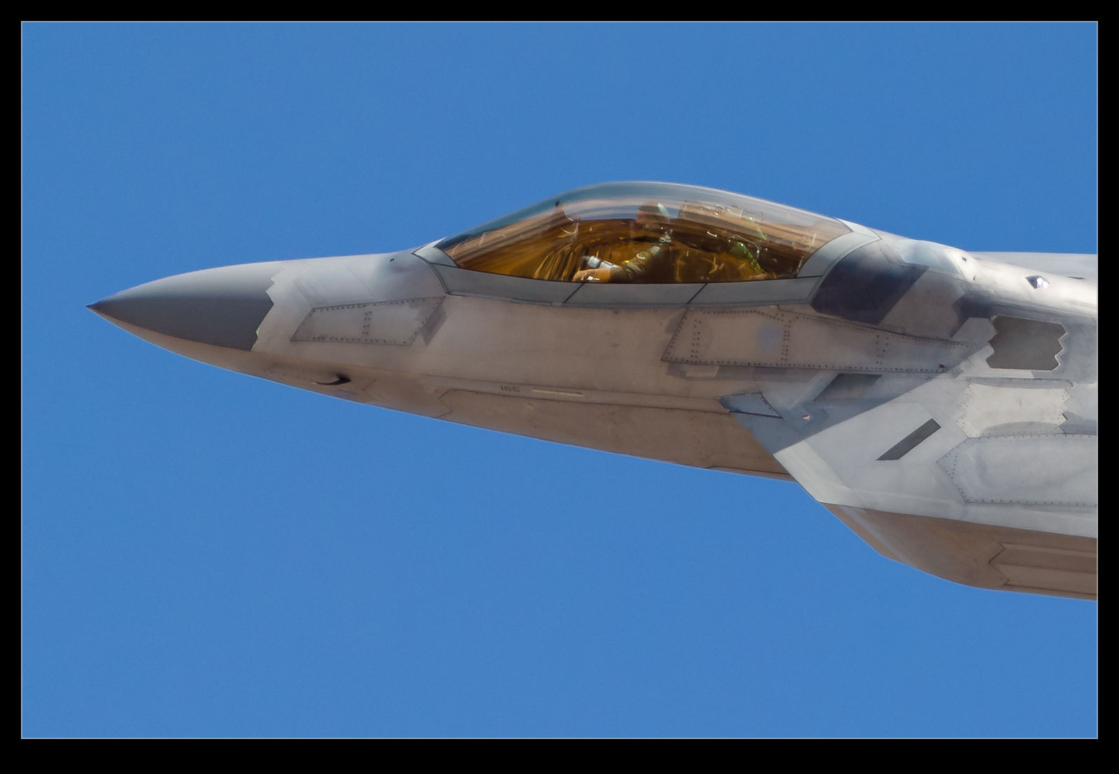 A USAF F-22A turns towards the ranges after takeoff from Nellis AFB as part of a Red Flag mission.